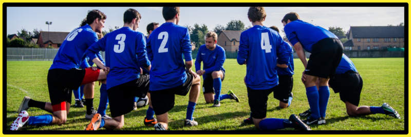 Group of young footballers kneeling on pitch- Do you need sports club insurance?