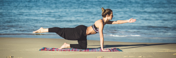 Young woman doing some yoga on a beach
