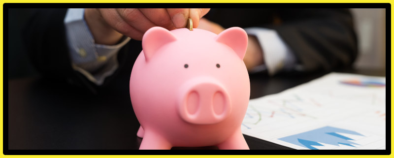 Businessman placing coin in a piggy bank saving funds.